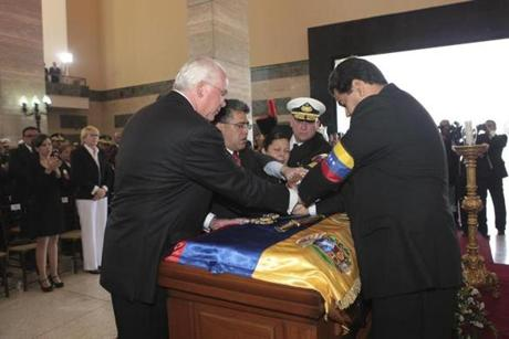 Venezuelan Vice President Nicolas Maduro (right) stood with ministers and the armed forces over the coffin.