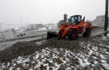 A front-end loader cleared rocks and debris from flooding from Ocean Street in Marshfield.