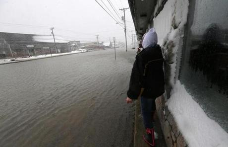 Kathy O'Brien made her way along the flooded Esplanade in the Brant Rock section of Marshfield.