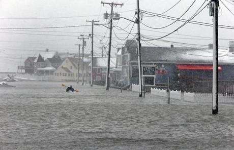 Kayakers paddled down the flooded esplanade area of Brant Rock in Marshfield.