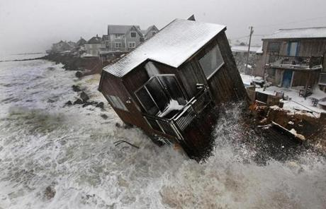 A house on Plum Island toppled shortly after 8:30 a.m.