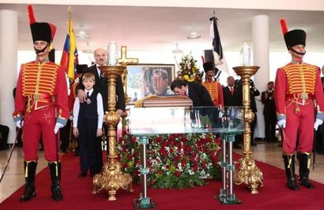 Mahmoud Ahmadinejad kissed the coffin of Venezuelan President Hugo Chavez as President Alexander Lukashenko of Belarus and his son stood next to it during the funeral.