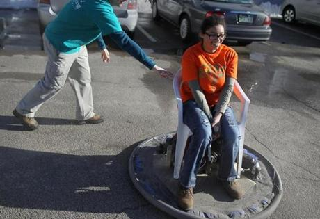 Instructor Rob Shamitz with Brianna Callanan as she rides on a hovercraft that she and other kids built in the science/engineering workshop.