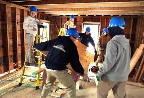 Blue Hills Regional Vocational Technical High School students carried a cut piece of plywood off sawhorses.
