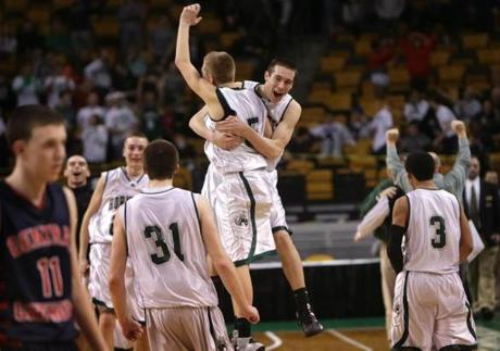 Mansfield players celebrated their 55-50 win as a disappointed Tyler Nelson (11) of Central Catholic walked the court after the D1 MIAA boys basketball state semi finals at TD Garden. Mansfield advanced to the state championships.