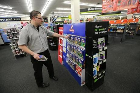 Assistant manager Cesar Solares arranged the income tax software display at a Staples in Somerville.