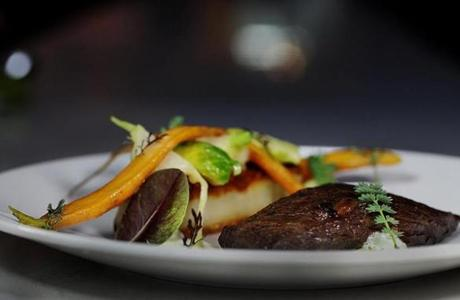Wagyu steak with slender carrots, turnips, and Brussels sprouts on a griddled cake of thinly sliced potatoes.