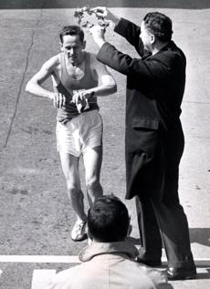 4/19/1960 Paavo Kotila, 32, of Finland reaches out to break tape with his fingers as he walks across finish line to win 64th annual Boston AA Marathon. Deputy Mayor John P. McMorrow holds aloft the wreath of victory. Kotila ran away form a field of 166 to win the 26 mile 385 yard grind in time of 2:20:54. The two-times champion of Finland had such a big lead he walked the last few yards. Library Tag 04162010 -- Marathonhistory
