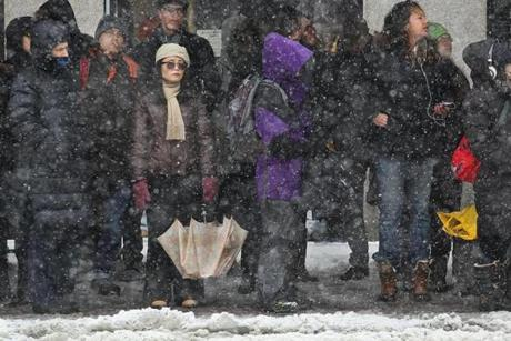 A problem with the T had commuters jammed up under bus shelters waiting for transport by bus on Massachusetts Avenue during Friday's snowstorm.