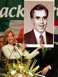 Lt. Governor Kerry Healey held up an altered photo of Thomas Finneran sporting Mitt Romney's hair at the 2005 breakfast.