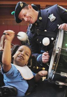 Brighton, MA 031513 At Franciscan Hospital for Children in Brighton, student Shifaia Gelato (cq), 7, and Patrolman Paul Caraher (cq) played the drums during a visit by the Boston Police Gaelic Column Pipes & Drums in honor of St. Patrick's Day, Friday, March 15 2013. (Staff Photo/Wendy Maeda) section: Metro slug: 16bagpipers reporter: In-Cap
