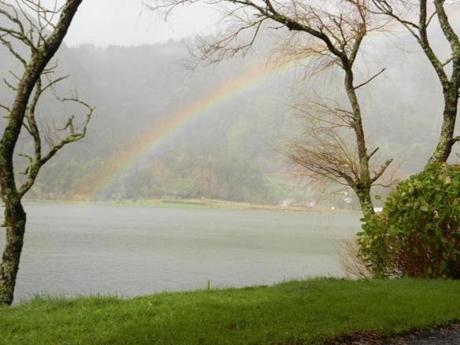 LAKE EFFECT SHOW A rainbow forms over Lagoa das Furnas, a volcanic crater lake on Sao Miguel.