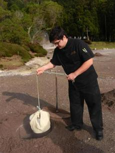 Local chef Paulo Costa lowers a wrapped pot filled with meats and vegetables into the hot earth for slow cooking. San Miguel, Azores