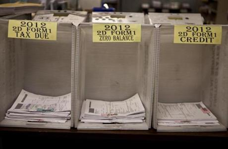 Bins are used to sort and organize 2012 paper tax returns at the Department of Revenue facility in Chelsea.