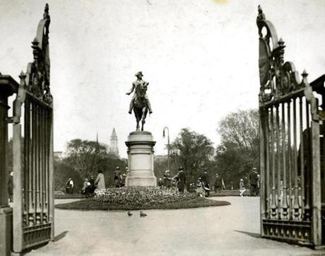 July 22, 1923:  The equestrian statue of George Washington in the Public Garden is seen through the gate opening from Arlington Street. The bronze statute by Thomas Ball, a sculptor from Charlestown, was dedicated on July 3, 1869. The Custom House Tower stands out in the background.