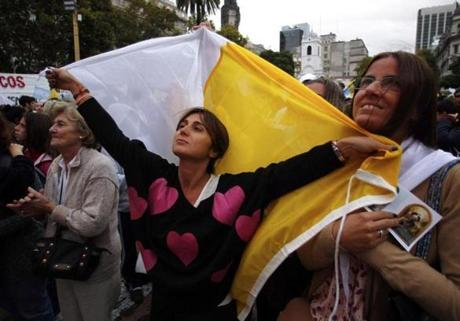 A woman held a Vatican flag as she watched the broadcast in Buenos Aires.