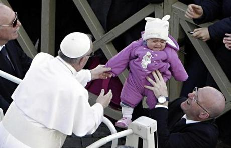 Pope Francis reached for a child during his tour through St. Peter's Square at the Vatican.