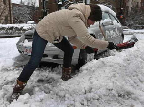 Olivia Kelly shoveled out her car with a window scraper on Commonwealth Avenue in Boston.