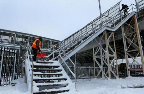 A worker cleared snow from the stairs at the JFK MBTA station in Boston.