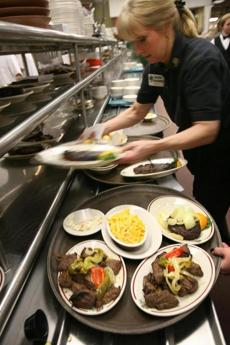 Server Sue Henderson, cq, of Hamilton, prepares to serve a table at Hilltop Steak House.