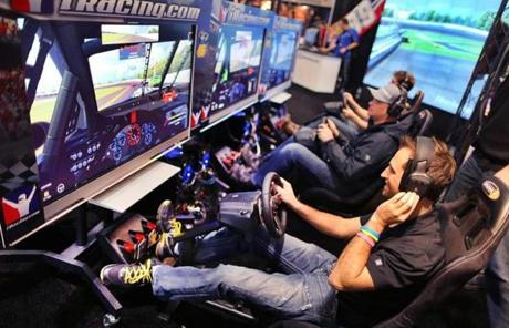 Conference-goers at the wheels of the iRacing.com game.