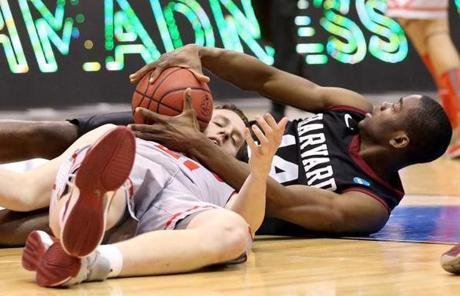 Cameron Bairstow of the New Mexico Lobos and Steve Moundou-Missi of the Harvard Crimson battled for a loose ball.