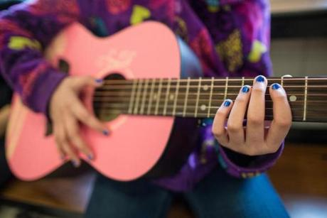 A student played a pink guitar.