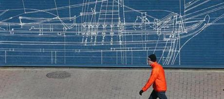 BOSTON, MA. 03/ 25 /13: ALL RIGGED UP....a mural on the doorway of a ship has a pedestrian bundled up from the cold by Commonwealth Pier in Boston's Seaport District. ( David L Ryan/Globe Staff Photo ) SECTION: METRO TOPIC stand alone photo