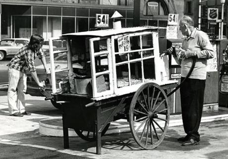 September 10, 1974: This popcorn vendor refueled his gas powered popper at a Columbus Avenue station before his day's work pushing the cart.