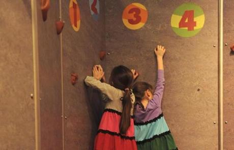 Sisters Caty Beard, 7, and Rose Beard, 5, of Holliston, play on the rock-climbing wall.