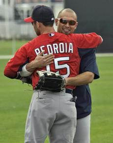 Dustin Pedroia hugged new teammate Shane Victorino during a workout early in spring training.
