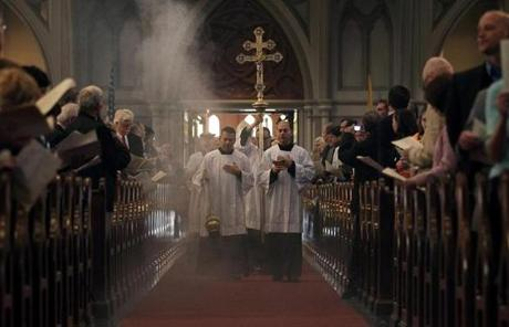 Congregants stood as the processional began for Easter Mass at the Cathedral of the Holy Cross.