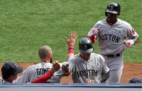 Jose Iglesias (foreground) and Jackie Bradley (background) were greeted by teammates after scoring in the second inning.