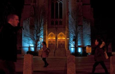 Marsh Chapel at Boston University was lit blue as pedestrians passed by.