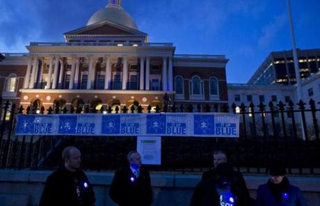 State officials and autism advocates gathered in front of the State House wearing glowing blue buttons.