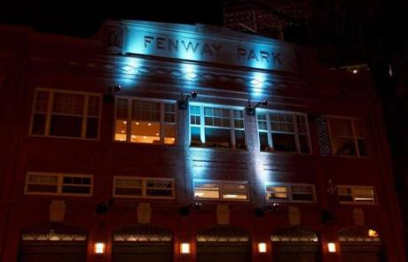 Blue lights highlighted the facade of Fenway Park's Gate A.