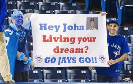 Blue Jays fans held up a sign referring to former manager John Farrell prior to the start of a game against the Red Sox on Friday night.