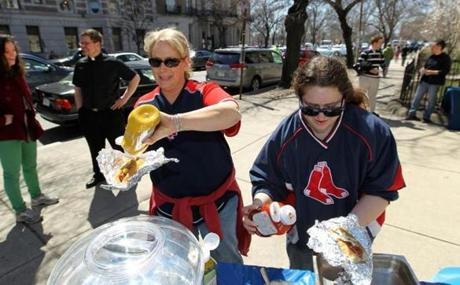 Boston, MA--4/8/2013--As Father Tom Carzon (cq) chats in the background, Michele Gervais (cq), left, and her daughter Rachel Gervais (cq), from Sandwich, dress their dogs. Seminarians and priests at St. Clement Eucharistic Shrine grill and hand out free hotdogs, as Red Sox fans head to Fenway Park for the opening day game, on Monday April 8, 2013. The Oblates of the Virgin Mary (cq) had about 500 hotdogs available and had given out about 300 before game time. Located at 1105 Boylston Street, seminarians were accustomed to seeing fans stream by in years past. This is the first year they decided to greet people and introduce them to the church. Photos by Pat Greenhouse/Globe Staff Topic: 09hotdogs Reporter: XXX