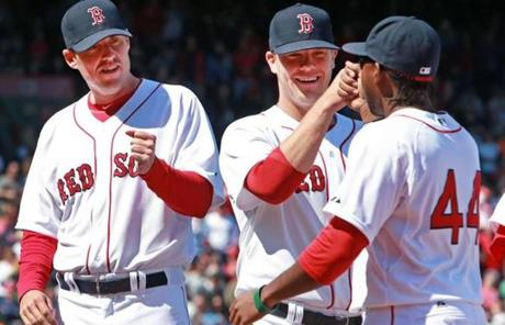 Red Sox pitchers John Lackey (left) and Andrew Bailey (center) greeted  Jackie Bradley, Jr. during pre-game player introductions.