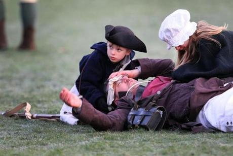 April 15, 2013-LEXINGTON--- PATRIOTS' DAY LEXINGTON, MA --Quinn,8, and Joleen Ricci, (cq) 11, of Bedford ,comfort their father Peter Ricci (cq) who plays John Tidd, who lays wounded after the British and Minute Men fought on Lexington's Green during re-enactment Monday morning. (globe staff photo: Joanne Rathe The Boston Globe metro )