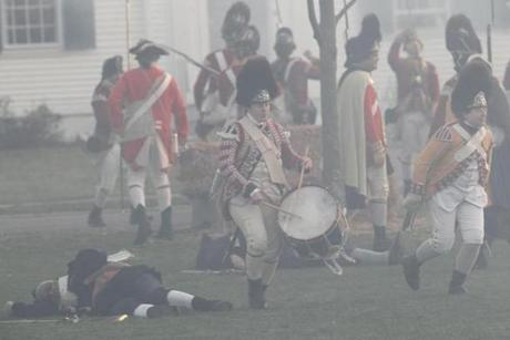 April 15, 2013-LEXINGTON--- PATRIOTS' DAY LEXINGTON, MA - Smoke from muskets fill the air as British soldiers march back over the dead and wounded Minute Men after engaging in battle during re-enactment Monday morning- (globe staff photo: Joanne Rathe The Boston Globe metro )