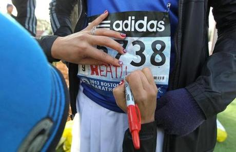 Varinka Ensminger, coach of Team Hoyt, wrote Heather Ekola's name on her bib.