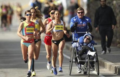 Women's Elite class runners passed Dick and Rick Hoyt, a father-son team that has become an icon of the marathon.