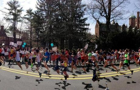 Runners make their way by Wellesley College on Route 135.