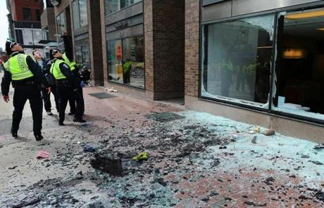 Boston Police examined blown-out windows at the scene of the first explosion.