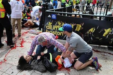 A woman received help at the scene of the first of two explosions on Boylston Street Monday. Medical workers at the finish line treated life-threatening wounds and losses of limbs.
