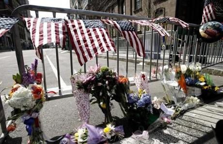 Flowers and American flags at a police barricade.