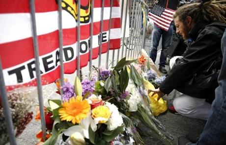 A man kneeled by flowers and a 'Don't tread on me' flag.