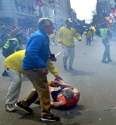 A marathon official helped the runner who was thrown to the ground by the initial blast.