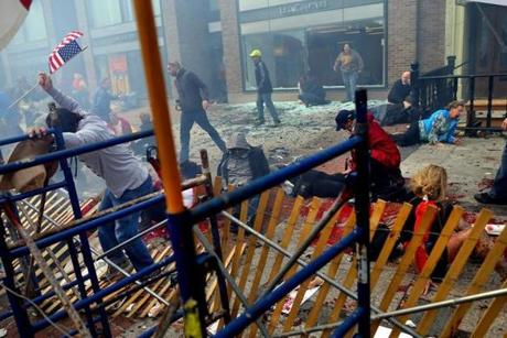 To reach the injured, bystanders had to tear down a makeshift fence that had been built for the marathon.